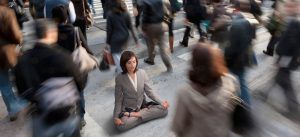 BX2EBA Mixed race businesswoman practicing yoga in busy urban crosswalk